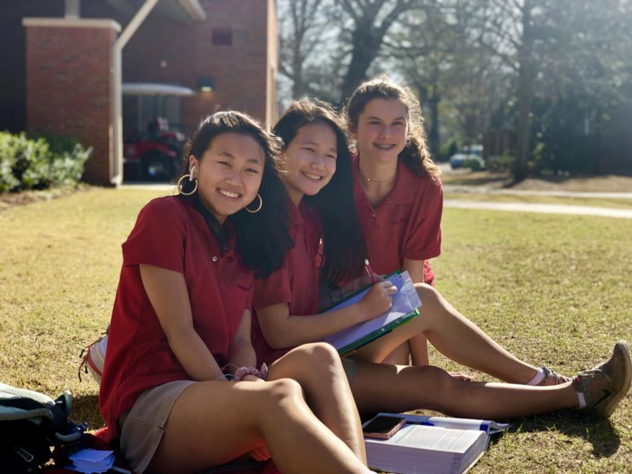 Suzanne, Emi, and Abby are excited to have English class outside.